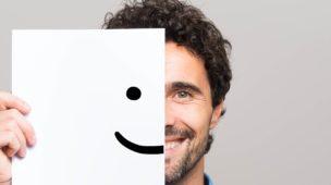 imagem de um homem de barba curta segurando um papel que representa a outra metade de seu rosto