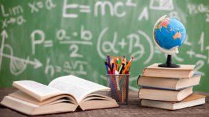 Imagem de uma mesa em sala de aula contendo livros empilhados, um pote de lápis, e um livro aberto. Ao fundo um quadro negro com fórmulas matemáticas.
