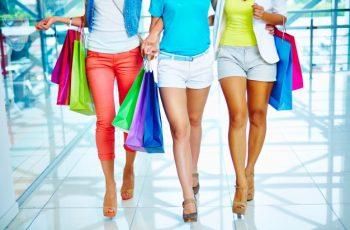 três clientes andando no shopping, cheias de sacola, na imagem não aparece o rosto das clientes