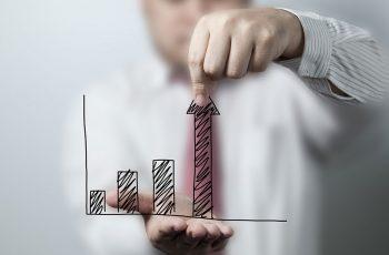 Executivo com um gráfico na frente demonstrando crescimento nos resultados